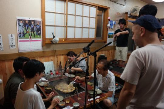 『tsu-na-ga-ruのボッタ』をレコーディングしたときの様子(2017)。ボッタは千住地域で親しまれていた駄菓子のひとつで、一般的にもんじゃとは異なり、水と小麦粉を溶かしたものでほとんど具材は入っていない。 写真:小野澤峻